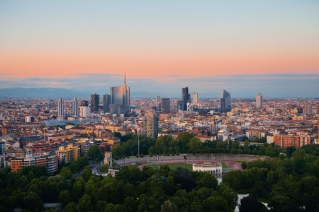 Milan city skyline with business district office building viewed from above at sunset in Italy.