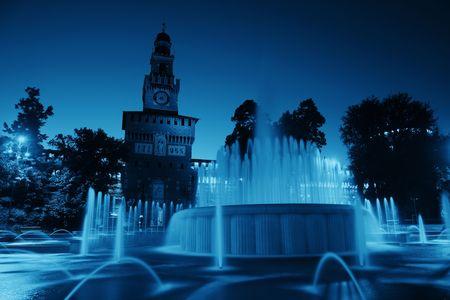 Landmark Sforza Castle and fountain in Milan, Italy at night.