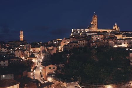 Siena Cathedral and Torre del Mangia Bell Tower with historic buildings. Italy. at night Stok Fotoğraf