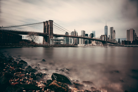 Pebble beach with Brooklyn Bridge and downtown Manhattan skyline in New York City