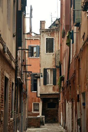 Alley view with historical buildings in Venice, Italy.
