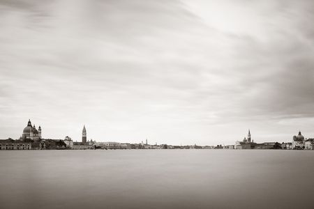 City skyline of Venice with clock tower and dome in long exposure viewed from waterfront in Italy. Stok Fotoğraf