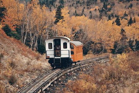 MT Washington, NEW HAMPSHIRE - OCT 13: Tourism train at mountain range with foliage on October 13, 2015 in New Hampshire. Mt Washington is the highest peak in Northeastern America. Editöryel