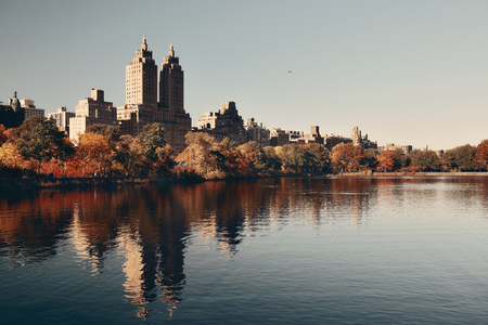 Skyline with apartment skyscrapers over lake in Central Park in midtown Manhattan in New York City Фото со стока