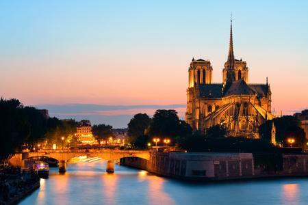 Notre Dame de Paris at dusk over River Seine as the famous city landmark. 写真素材