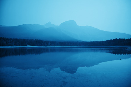 Lake with fog and mountain reflections