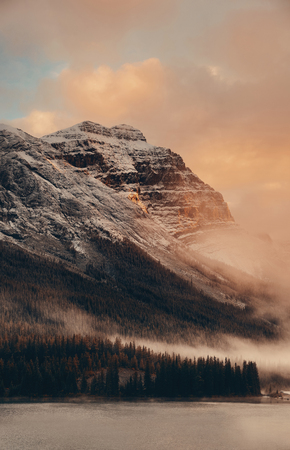 Snow capped mountain and fog at sunset in Yoho National Park in Canada