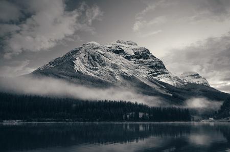 Montagna innevata con riflesso del lago in un crepuscolo nebbioso nel Parco Nazionale di Banff, Canada.