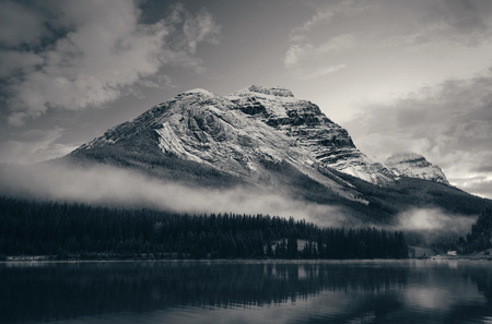Snow capped mountain with lake reflection in a foggy dusk in Banff National Park, Canada. Banco de Imagens - 116734912