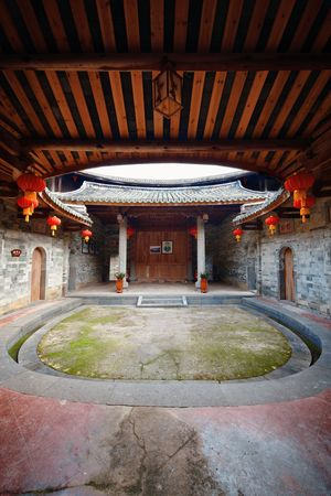 FUJIAN, CHINA – MARCH 2, 2018: A courtyard in Tulou. Tulou is the unique traditional rural dwelling of Hakka. 스톡 콘텐츠 - 127377095