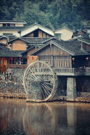 FUJIAN, CHINA – MARCH 2, 2018: Yunshuiyao old town by the river with watermill in Fujian, China. 에디토리얼