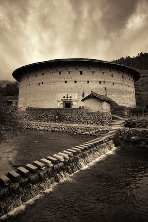 FUJIAN, CHINA – MARCH 2, 2018: Tulou building at waterfront. Tulou is the unique traditional rural dwelling of Hakka.