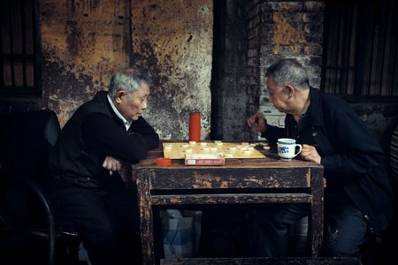 CHONGQING, CHINA – MARCH 13: Old men play chess on March 13, 2018 in Chongqing. The lifestyle of the old 80's is preserved in this Tea House as the famous tourism attracitions.