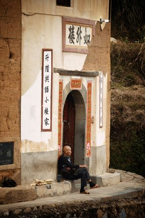 FUJIAN, CHINA – MARCH 2, 2018: Man rest at the entrance of Tulou. Tulou is the unique traditional rural dwelling of Hakka. Editöryel
