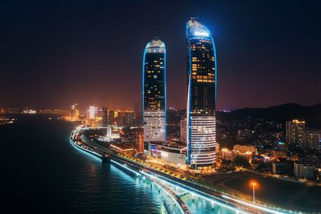 XIAMEN, CHINA – FEB 16: Shimao Twin Tower and city skyline night aerial on February 26, 2018 in Xiamen. Xiamen was ranked as Chinas 2nd-most suitable city for living