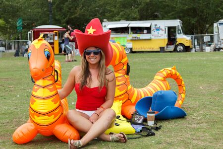 floaters: Portland, Oregon, USA - July 26, 2015: A woman dressed as a cowgirl relaxes at Tom McCall Park to ride her Sea Horse down the Willamette River at The Big Float