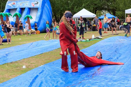 floaters: Portland, Oregon, USA - July 26, 2015: Playing on oversized slip and slides at the The Big Float along the Willamette River Editorial