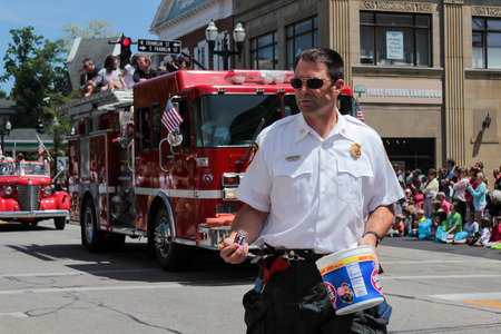 chagrin: Chagrin Falls, Ohio, USA - May 26th, 2013:  The Chagin Falls Fire Department coasts down the street handing candy to the eager children at  Blossom Time Parade, Chagrin Falls, Ohio Editorial