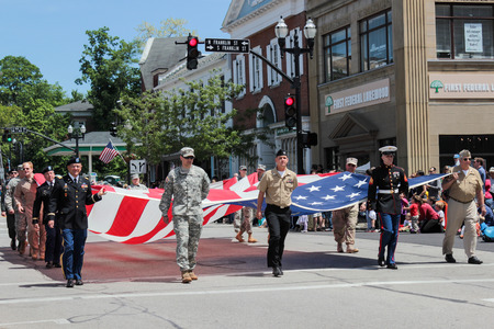 chagrin: Chagrin Falls, Ohio, USA - May 26th, 2013:  Local Chagrin Falls service men carry the United States to begin the Blossom Time Parade, Chagrin Falls, Ohio