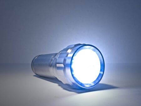 Concept image of a shining torch against a plain background