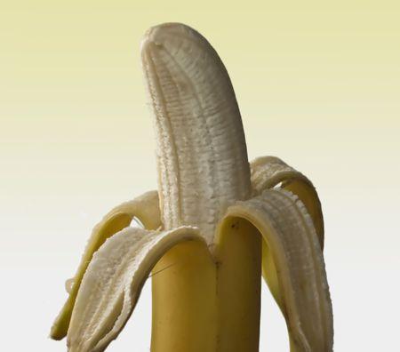 Peeled banana against a yellow graduated background Stock Photo
