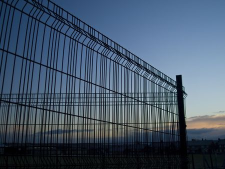 Wire fence pictured against a twilight sky