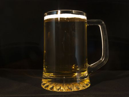 Half pint glass of beer against a black background