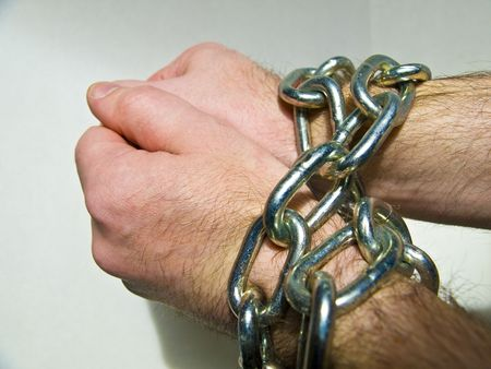 Pair of hands fastened together with chains  Stock Photo