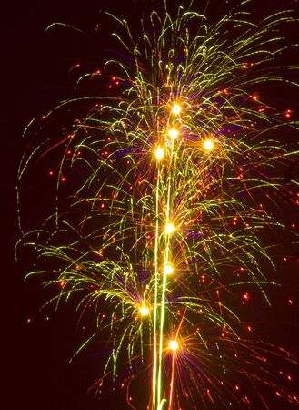 combust: Firecrackers exploding against a dark night sky Stock Photo
