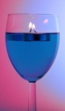 Floating candles in wine glass Stock Photo