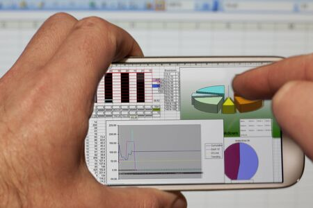 Male hands holding a smartphone and using a spreadsheet application in the office