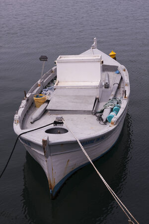 old fishing boat anchored in the harbor photo