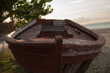 old wooden boat abandoned on the beach photo