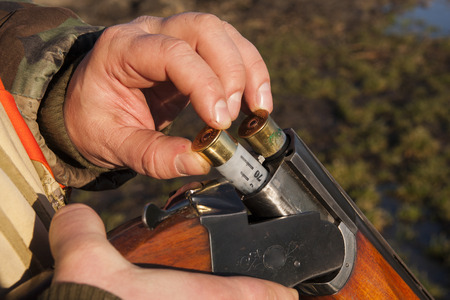emptied: hunter emptied his rifle ready to have breakfast in the countryside