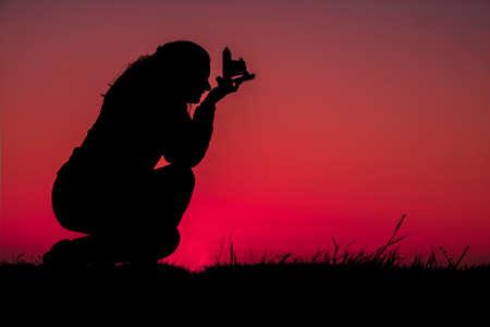 Young women with binoculars watching a beautiful sunset
