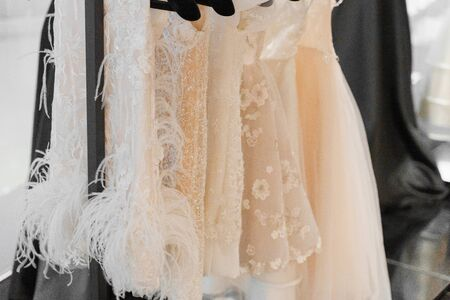 Little wedding dress for child on hangers made of silk chiffon, tulle and lace. White cream bridal dress for little princess. Pearls and crystals pendants on the sleeves of a wedding dress
