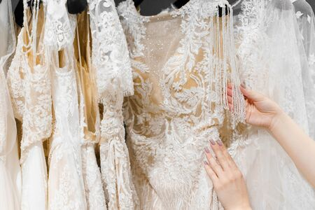 Bride touches luxurious white cream wedding dress on hangers. Dresses made of silk chiffon, tulle and lace. Luxury pearls and crystals pendants on the sleeves of a delicate color of a wedding dress