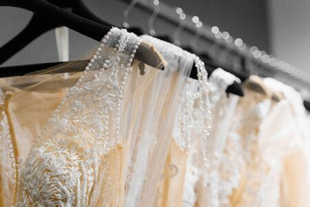Cloth of wedding dresses made of silk chiffon, tulle and lace. Beautiful White cream bridal dress on hangers in wedding salon. Pearls and crystals pendants on the sleeves of a wedding dress Foto de archivo