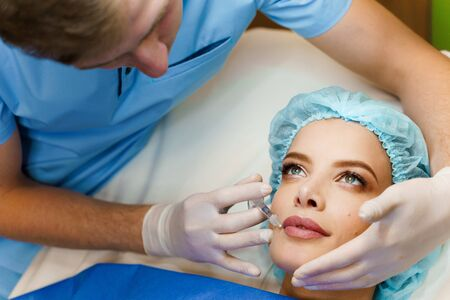 Closeup lips augmentation injections for attractive girl. Plastic surgeon does injection in lip in medical clinic. Cosmetic rejuvenating facial treatment. Empty space for advert Foto de archivo