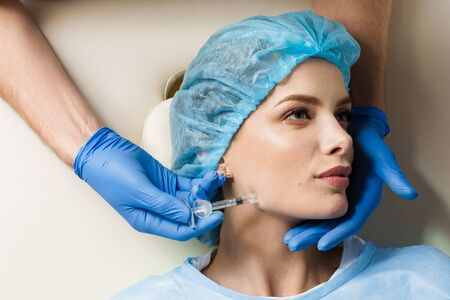 Filler injection of hyaluronic acid. Contour plastic for correcting the volume and shape of the nose, chin, cheekbones, temples. Cosmetic rejuvenating facial treatment in medical clinic