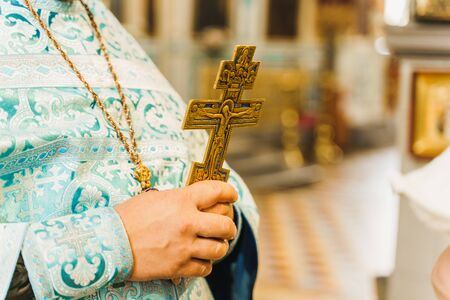Holy father in his robe with a golden cross in his hands in church. Orthodox tradition and faith. Equipment for praying. Pray for people life. Pray to god