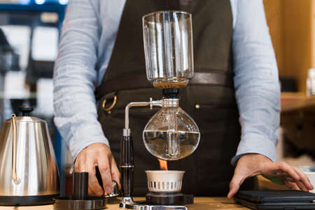 Coffee brewing by Syphon device. Close up syphon is heating by fire. Brewing photo on the fire. Alternative method of coffee making.