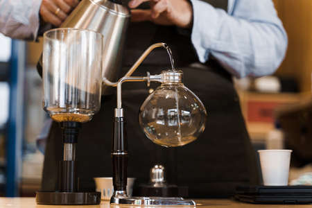 Syphon alternative method of making coffee. Barista pours hot boiling water in syphon device for coffee brewing in cafe. Scandinavian method of coffee making. Banco de Imagens