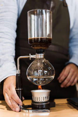 Syphon coffee brewing process. Close-up syphon is heating by fire. Barista looking at alternative coffee brewing process on the fire. Advert for social with empty right side for text of advertise Stockfoto