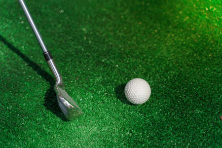 Close-up golf sport game with niblick and white ball on the green grass. Playing in mini golf. Empty place for advert right side.