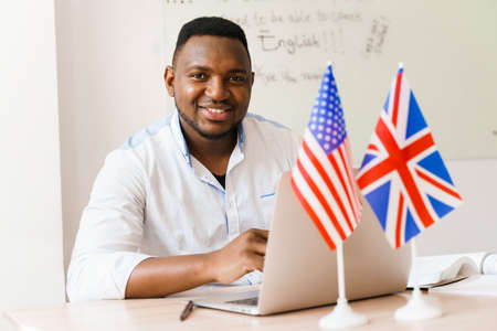 Black handsome man smiles, grimacing and uses his laptop for online work according social distancing. Speaking by web camera with colleagues. Scientist works at home on quarantine period. Zdjęcie Seryjne