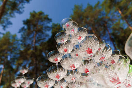 Big pyramid of glasses with champagne and red cherry inside on business meeting at summer day in the forest. Drink coctkail catering for wedding