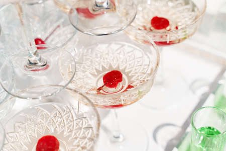 Red cherry close-up inside wine glass in pyramid of champagne. Drink catering for wedding ceremony. Alcohol cocktails for guests. Business meeting open air with social distancing Stock Photo