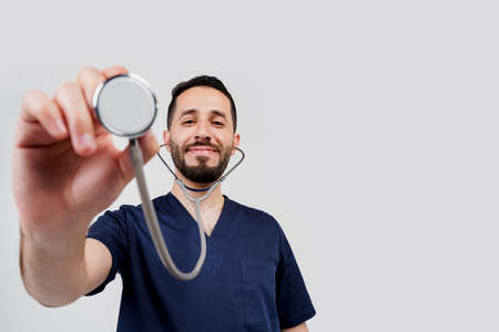 Smiley arabian doctor surgeon with stethoscope on white background. Professional arab medecine. advert for medical clinic Stok Fotoğraf