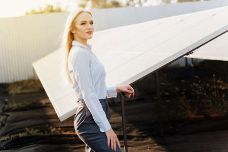 Girl stand near solar panels row on the ground with sun light. Woman investor wears formal white shirt. Free electricity for home. Sustainability of planet. Green energy.